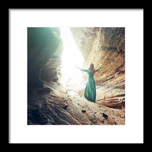 Young blonde woman in green dress found the way out from the cave