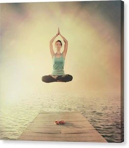 Young woman floating in the air in lotus asana position near the sea