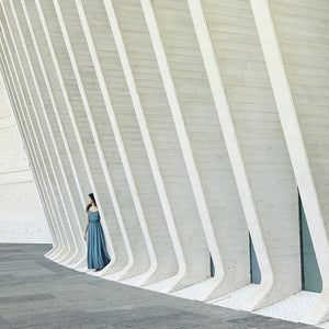 Young woman in blue dress hiding in the modern building walls