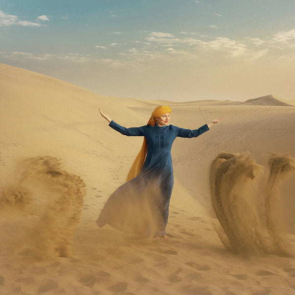 Desert woman in blue dress and yellow turban raises sand in the air
