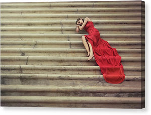 Young woman in red dress is laying down on stairs