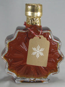 Snowflake shaped glass bottle filled with natural maple syrup with gift tag
