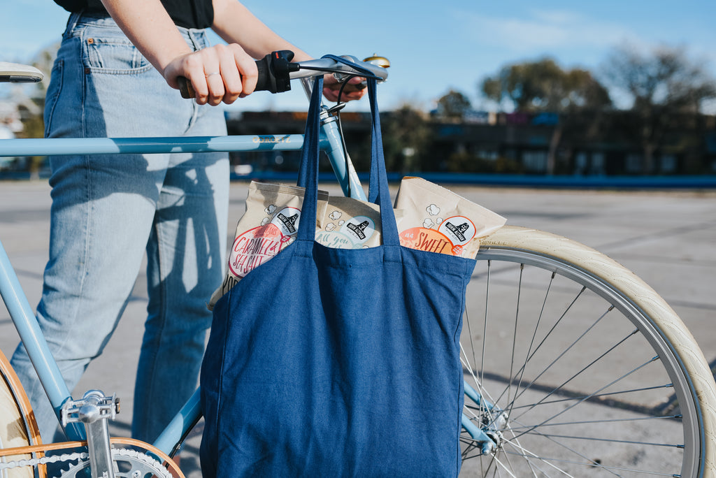A person with a light blue bike carrying a dark blue bag full of popcorn.