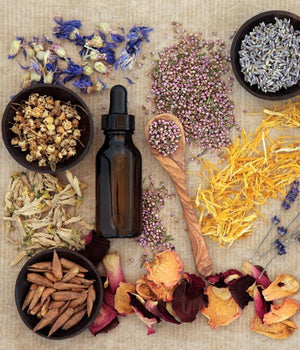 Natural therapy utensils, vial, herbs, and flowers