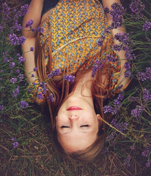 A woman laying with closed eyes in a field of lavender