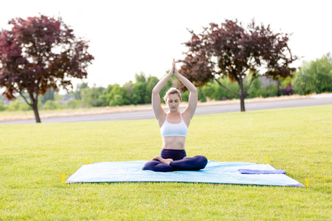 A young woman practicing yoga in the park using the BeachSheetz outdoor blanket