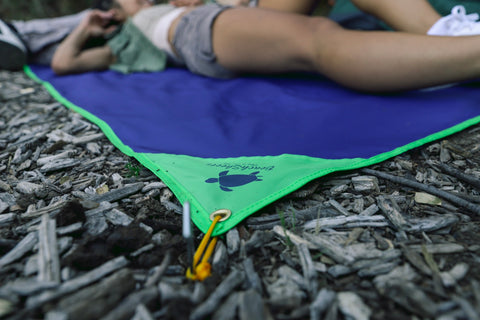 A couple using the ground stakes for their BeachSheetz Camp Blanket while camping