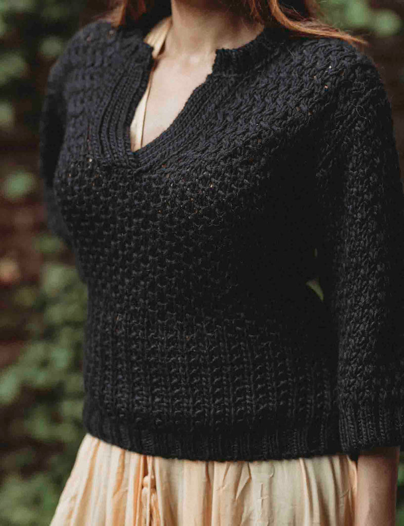 Close up of black wool sweater on top of a yellow dress side view