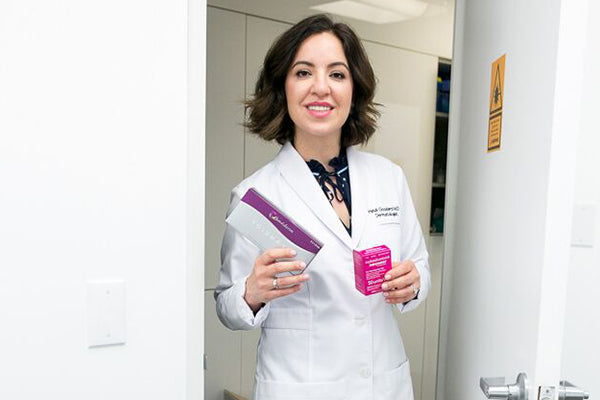 Dr. Heidi in her white coat holding her injectable filler products.