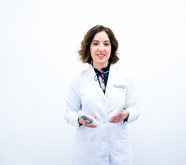 An image of Dr. Heidi in her white coat with a fractional laser machine