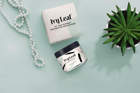 Jar of Ivy Leaf's Restorative Moisturizer and product box beside potted plant and string of pearls against a sea green background, for Ivy Leaf Skincare