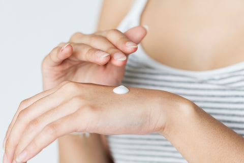Woman applied dime-sized amount of white cream moisturizer to the back of her hand, for Ivy Leaf Skincare
