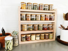 Load image into Gallery viewer, Little Label Co Pantry jars with labels sitting in the timber pantry rack. The shelf sits on a grey stone bench with white subway tiles behind. A plant and some jars sit to the left.