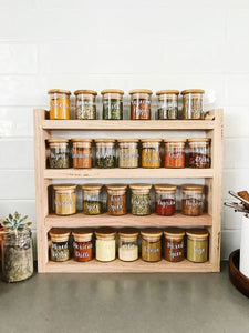 The timber spice rack sits on a grey stone bench with white subway tiles behind. The spice rack is filled with Little Label Co jars and labels.