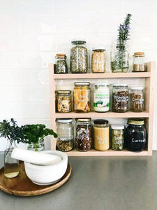 Pantry jars sitting in the timber pantry rack. The shelf sits on a grey stone bench with white subway tiles behind. A white mortar and pestle sits to the left.