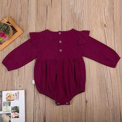 Ruby romper for baby girls, laying flat on wooden backdrop