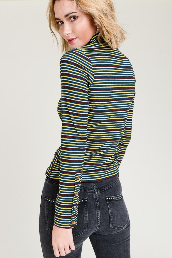 Woman wearing teal striped turtle neck top side view