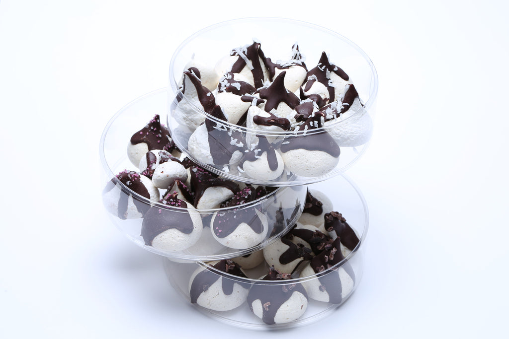A three-tiered set of chocolate-dripped meringues: vanilla bean, chocolate, and maple meringue kisses.