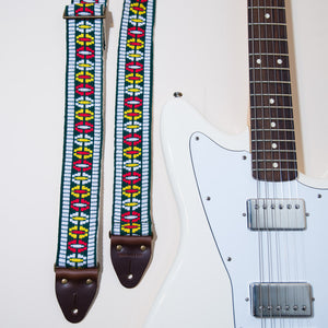The Vintage Guitar Strap in Rhododendron Ave with a white Fender Jaguar