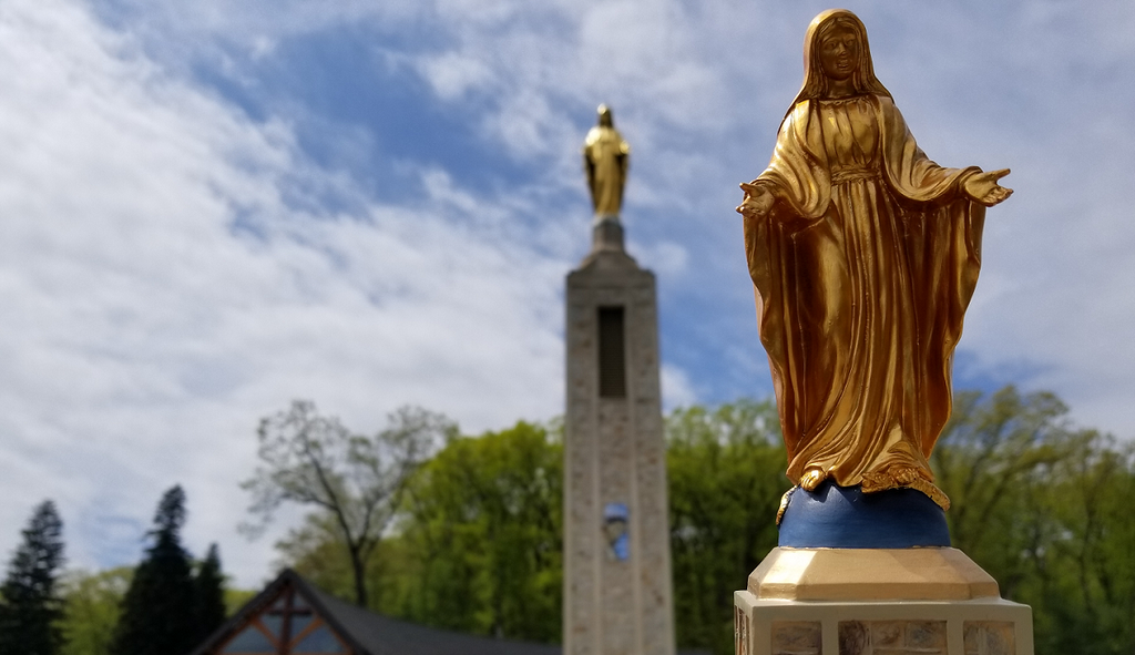 Replica golden statue of Mary with St. Bernadette's Shoppe in background and the real statue of Mary at the National Shrine Grotto in Emmitsburg Maryland