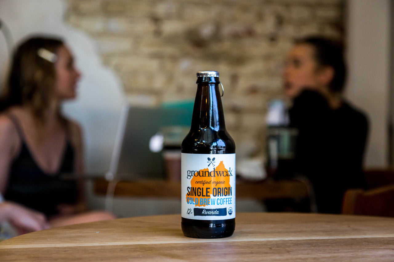 bottle of Groundwork Single Origin Cold Brew on table with people in background