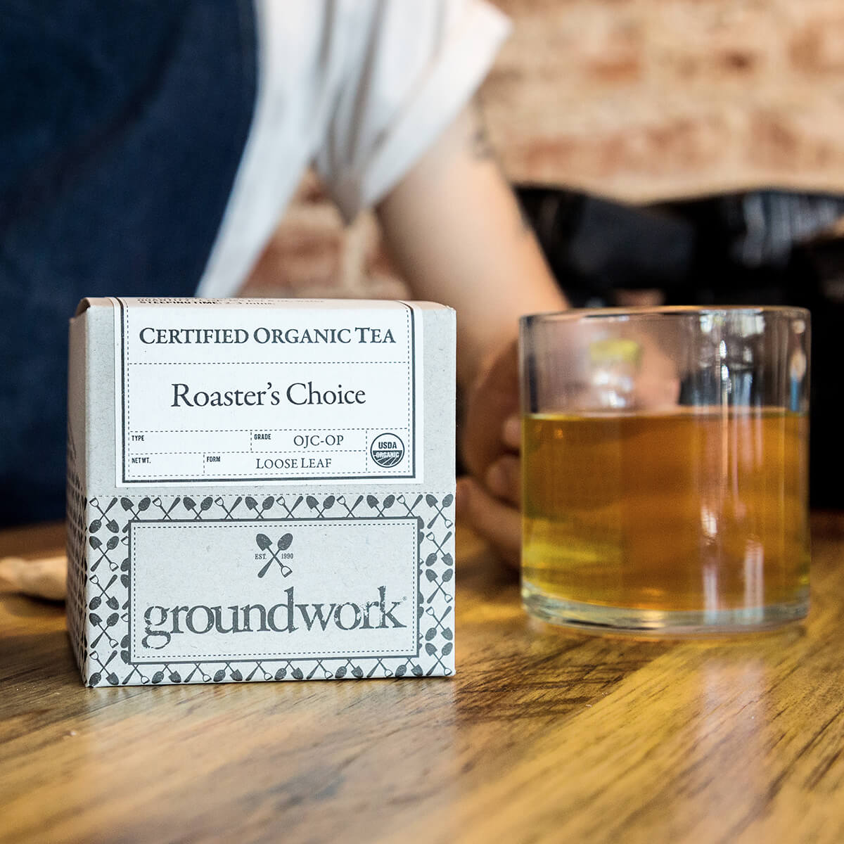 box of Groundwork Roaster's Choice Certified Organic Tea next to glass mug of tea