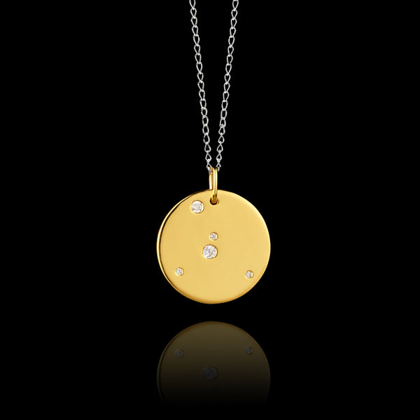 Close up of Cancer Zodiac star sign pendant in gold with silver chain. Made by British jewellery designer Catherine Zoraida