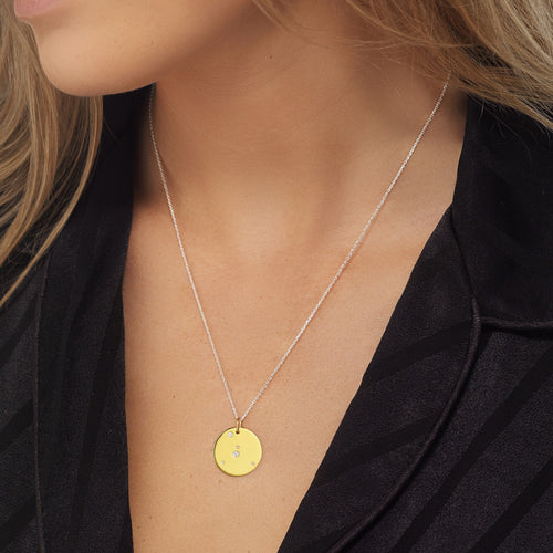 Cancer Zodiac star sign pendant in gold with silver chain. Model Lucy Williams