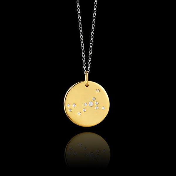 Close up of Scorpio Zodiac star sign pendant in gold with silver chain. Made by British jewellery designer Catherine Zoraida