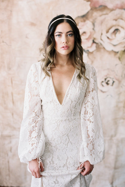 Danani Style #215 | Summer bride with long hair in soft curls wearing dreamcatcher fringe halo headband with tassels and macrame. Deep V lace wedding dress is Mojave by Elizabeth Dye. Hand painted wedding backdrop by Wildfield Paper Co. | Loblee Photography