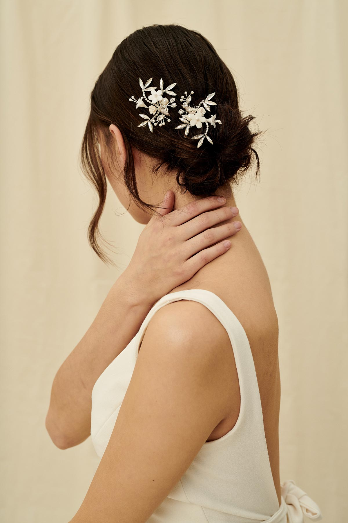 A silvery hairpin set with porcelain flowers, pearl beading, and glittery marquise crystals