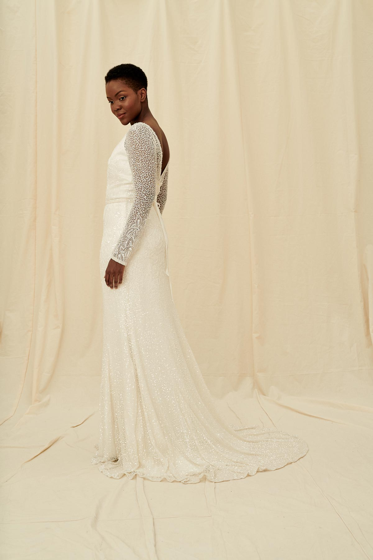 An elegant wedding gown with a fitted beaded skirt, sheer sleeves, and a deep v neckline and low back