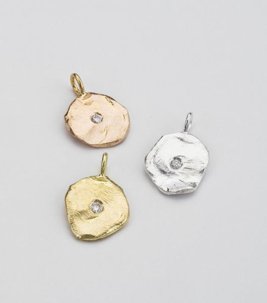 Perfectly Imperfect round gold pendant shown in rose, yellow and white gold.  Accented in the center with a white diamond.