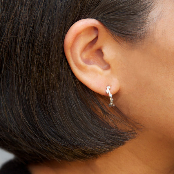 Small half hoop earrings on model - nature inspired in sterling silver.