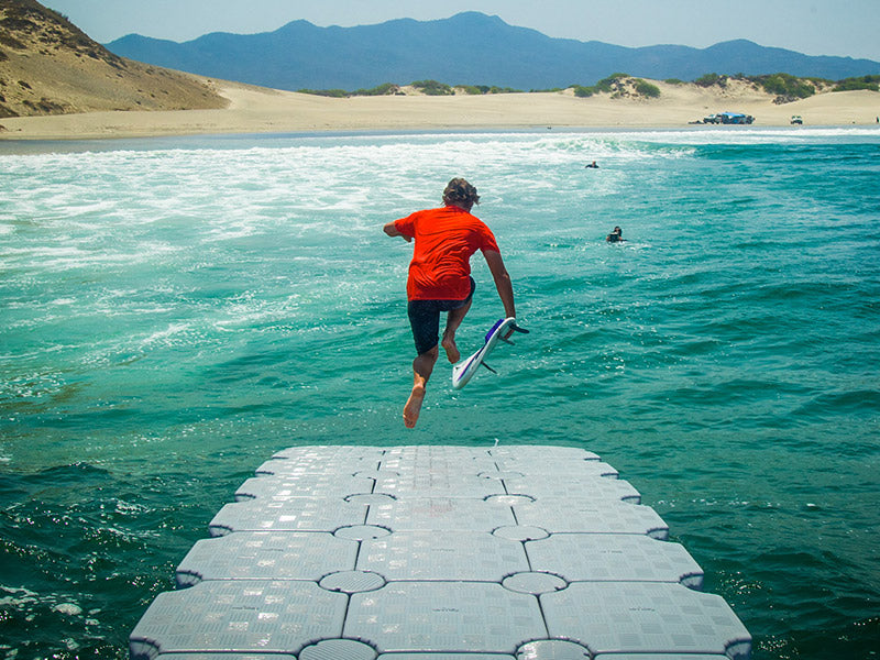 A Volcom team rider jumping off a Dock floating in the middle of the ocean.