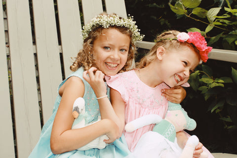 two laughing girls wearing pink and blue smocked dresses with flower crowns