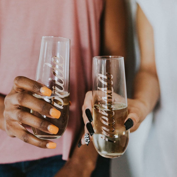 Bride and maid of honor holding cute personalized glass champagne flutes.