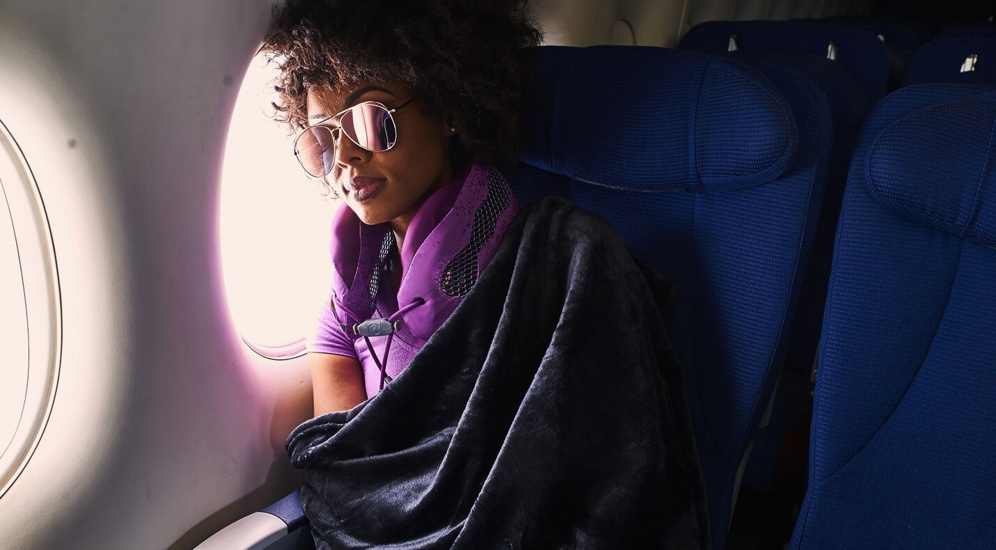 Woman wearing purple neck pillow sleeps against plane window