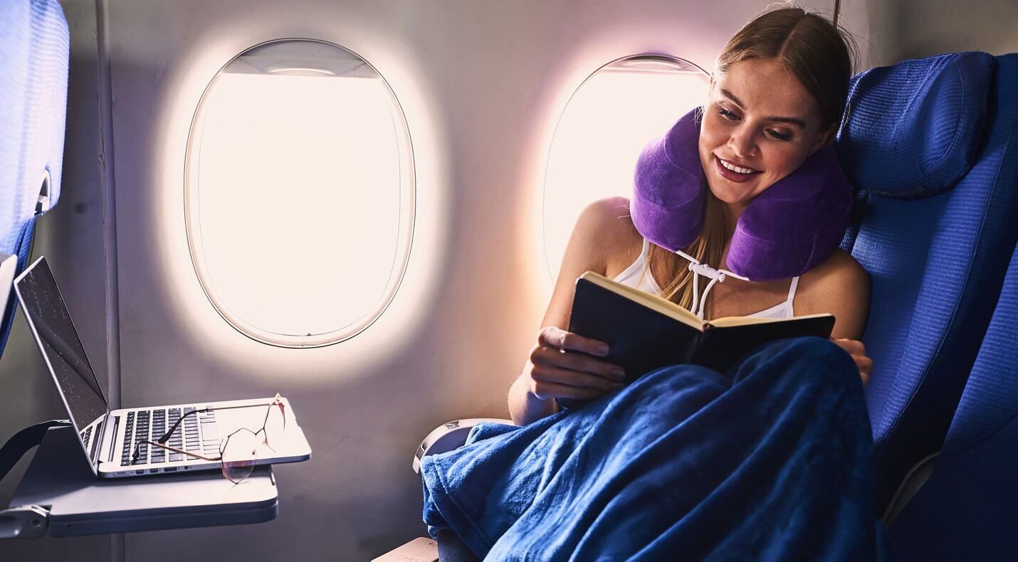 Woman with neck pillow on curls up in airplane seat with book