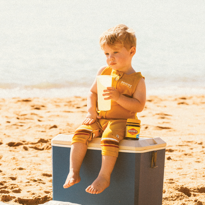 Cute boy at the beach sitting on esky wearing the My Brother John Ezra romper from the happy little vegemite collection drinking out of a retro cup