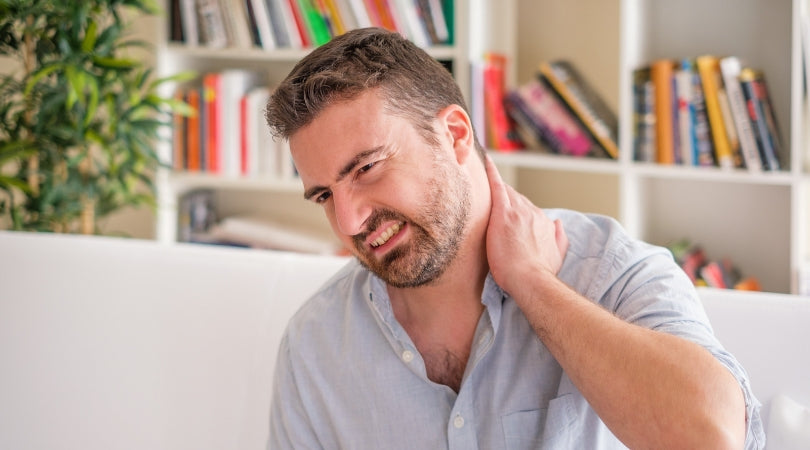 man with experiencing pain on the neck and shoulders