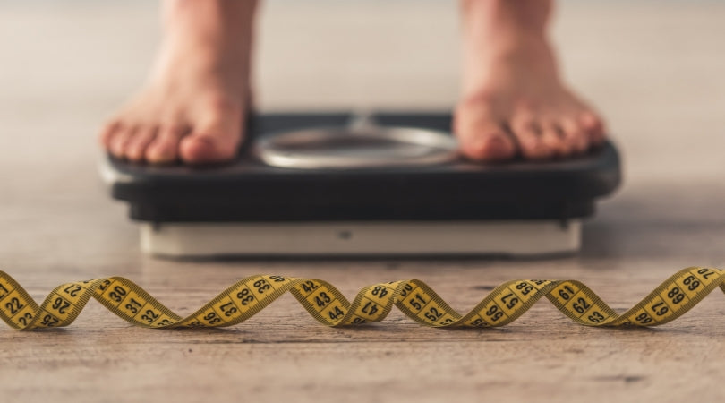 weight management showing person standing on weighing scale