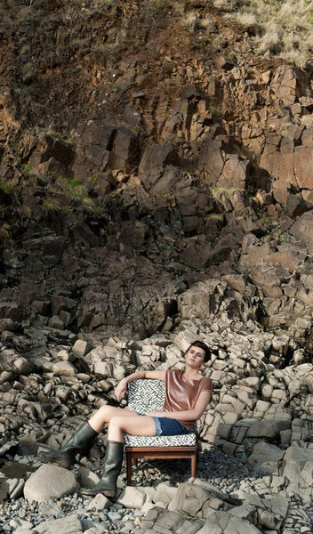 "Carley Kahn ""Checker"" upholstery fabric. Model reclining in upholstered chair on rocky beach against rocky cliff backdrop."