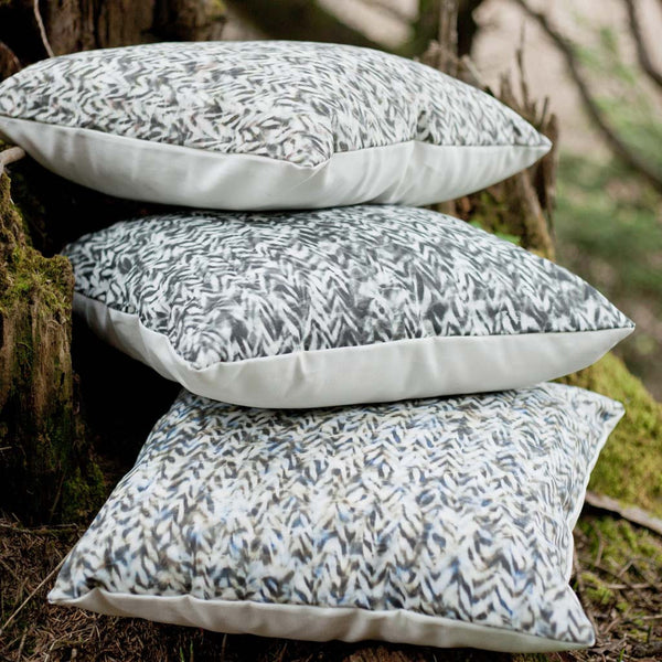 "Carley Kahn ""Chevron"" pillow covers. Three of them stacked on ground next to tree stump."