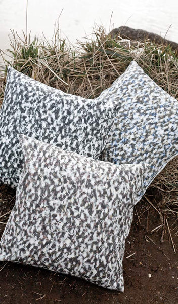 "Carley Kahn ""Scallop"" pillow covers. Three of them on grassy cliff overlooking ocean."