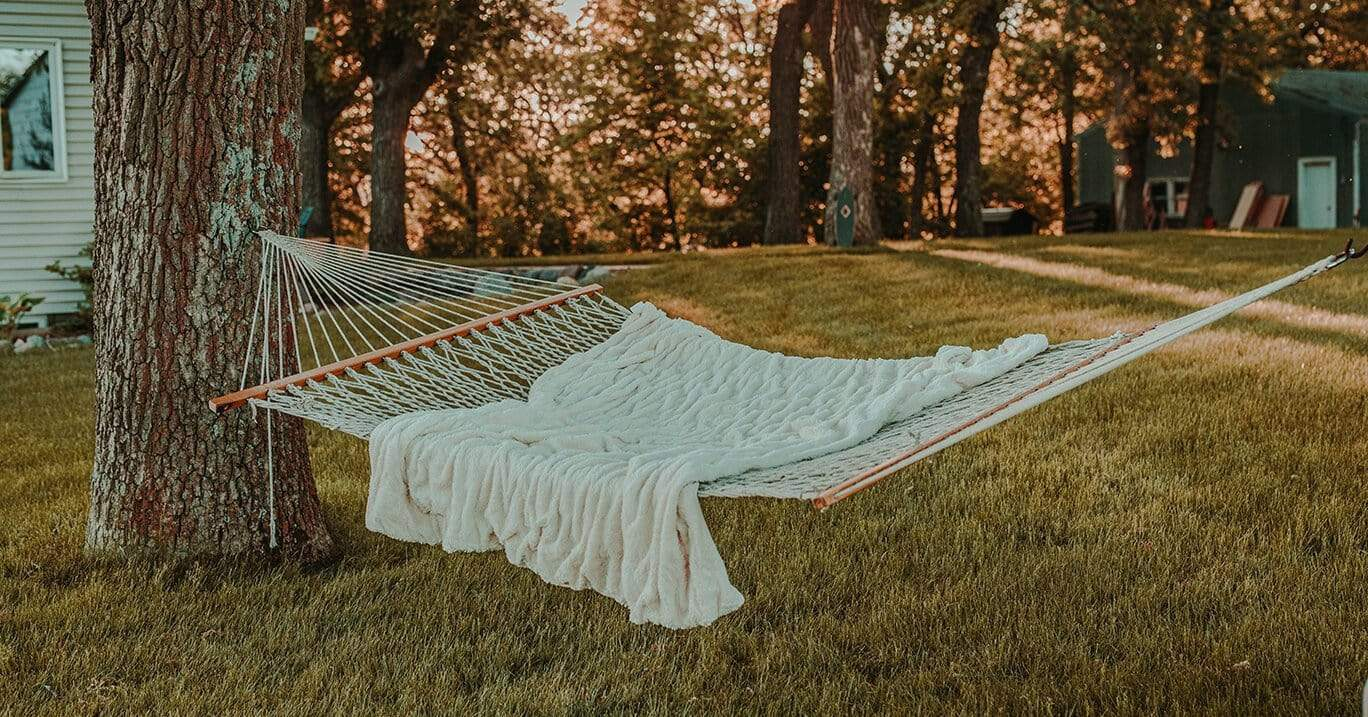 Cotton rope hammock with spreader bars hangs between trees in the backyard with a cozy blanket on it