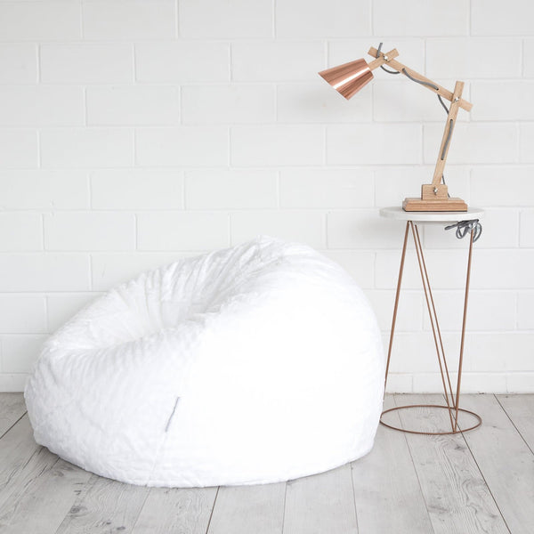 white plush beanbag on a wooden floor next to a copper table and lamp
