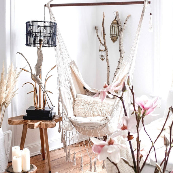 cream hammock chair hanging in a boho bedroom with magnolia flowers and candles