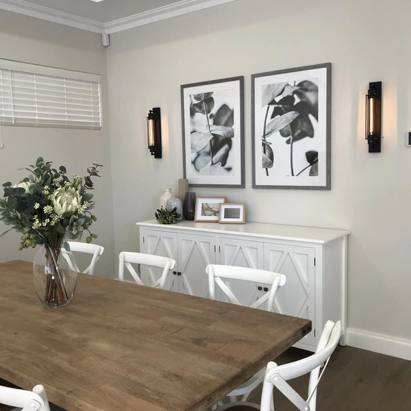 black wall sconce on a dining room wall with white chairs and flower prints on the wall