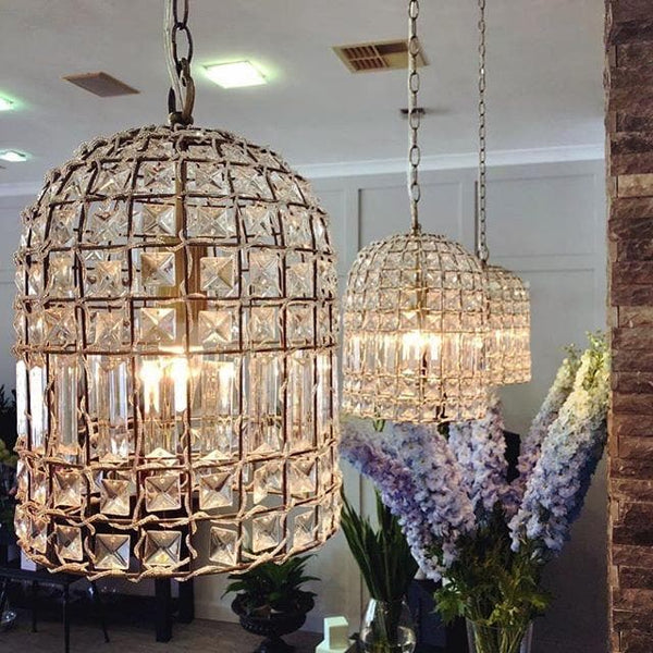 whitney brass gold chandelier in a dome shape with flowers in the background